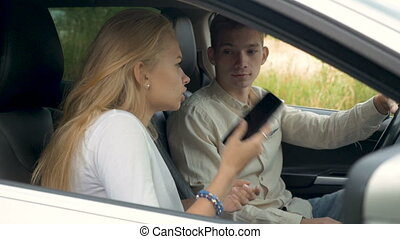 A young couple swears on a date, they are sitting in the car.