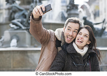 young couple taking a selfie of their grimaces