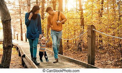 A young couple walks in the woods with a little boy