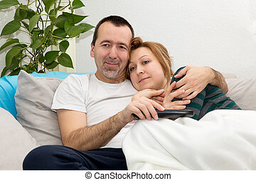 Couple watching Tv on a Sofa