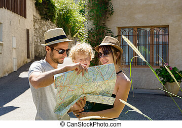 a young couple, with a child looking at a map