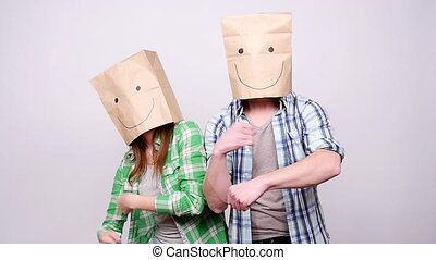 A young couple with paper bags on their heads is happy and dancing
