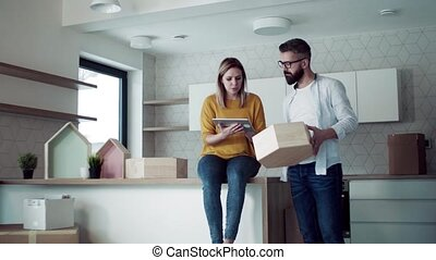 A young couple with tablet talking when moving in new home,...