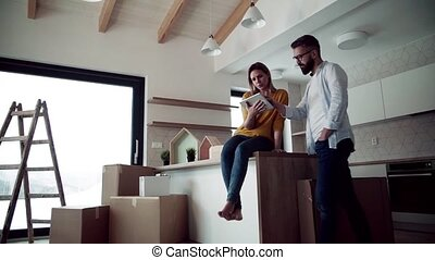 A young couple with tablet talking when moving in new home, planning.