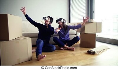 A young couple with VR goggles sitting on a floor, moving in...