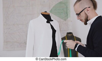 A young creative tailor makes measurements of a white jacket on a dummy in his studio for sewing clothes. The bearded fashion designer makes measurements of a new model of clothes he produces