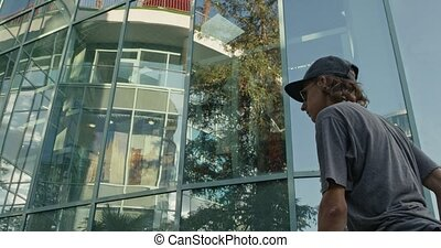 A young curly skateboarder riding around a new glass building. Slow motion