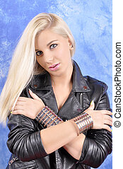 A young, curvy woman with arms crossed on her shoulders with wide bracelets.