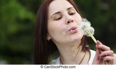 A young cute woman blowing on a dandelion against the backdrop of a summer green garden