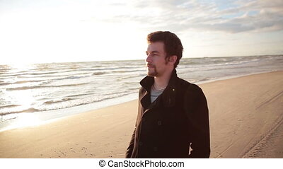 A young dark-haired man in a black coat is walking along the sea shore enjoying the view of the sea.