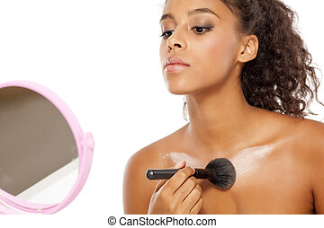 dark skinned woman applies a highlighter - a young dark...