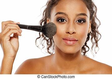 dark skinned woman applies a highlighter - a young dark...