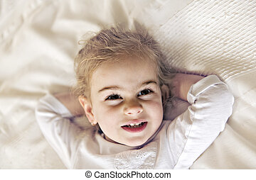 A young daughter two years old relaxing in bed, positive feelings