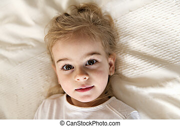 young daughter two years old relaxing in bed, positive...