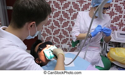 A young dentist works upper tooth of patient recorded by struts and cofferdam, nurse assists.