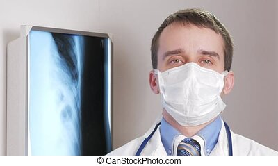A young doctor in a face mask looks at the camera and smiles. Against the background hanging x-ray of the patient. Shirt with a tie and a stethoscope on the neck