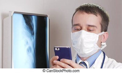 A young doctor in a face mask uses a phone in the clinic. A man records the results of a patient's x-ray.