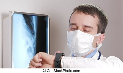 A young doctor in a face mask uses a smart watch in the clinic. The man dictates the results of the patient's x-ray.