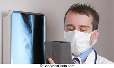 A young doctor in a face mask uses a tablet computer in the clinic. A man records the results of a patient's x-ray.