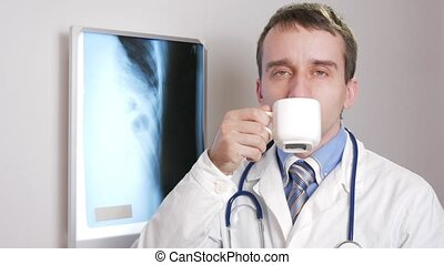 A young doctor looking at the camera is drinking a hot drink from a white mug. On the neck hangs a stethoscope.
