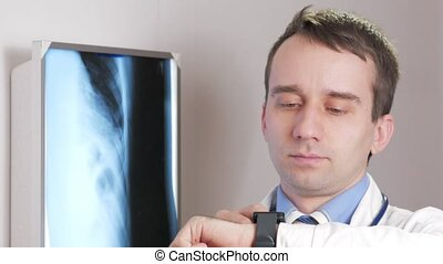 A young doctor uses a smart watch in the clinic. The man dictates the results of the patient's x-ray.