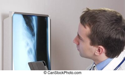 A young doctor uses a tablet computer in the clinic. A man records the results of a patient's x-ray.