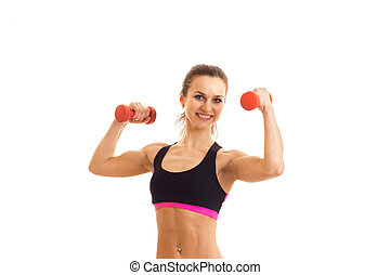 a young energetic girl in tank top and with dumbbells in your hands looks straight and smiling