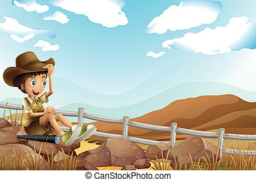 A young explorer sitting above the rock near the wooden fence