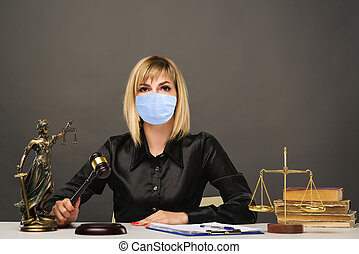 A young fair woman judge in protective mask works in her office. - image