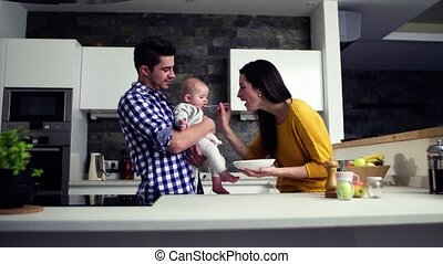 A young family at home, a man holding a baby and a woman...