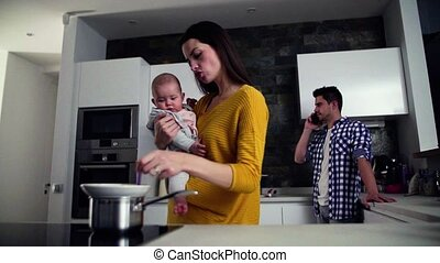 A young family at home, a man making a phone call and a...