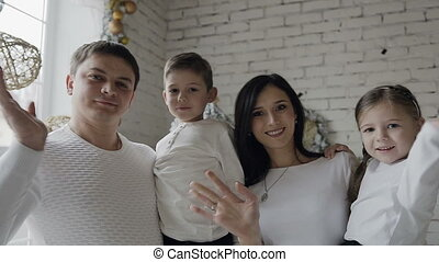 A young family on the background of a white wall looking into the camera and waving her hands greetings