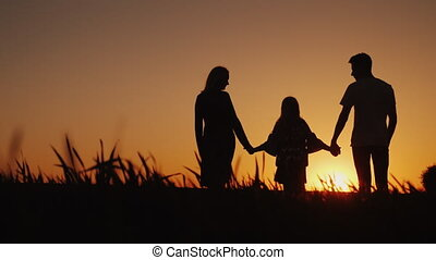 A young family with a child admiring the sunset, a back view...