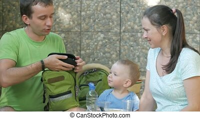 A young family with a child is measuring sunglasses on a baby. Mom dad and baby are sitting in the park cafe