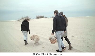 A young family with a daughter and a dog walking along the beach on a picnic. The dog stops and everyone looks at it.
