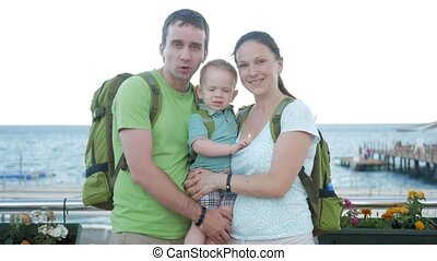 A young family with a toddler looking at the camera and smiling. Everyone has backpacks on their backs. The sea and the beach behind.