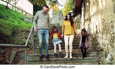 A young family with children on the stairs outdoors in town...