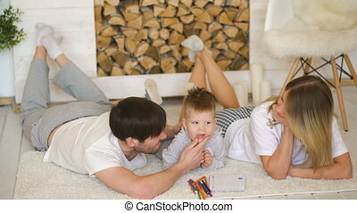 A young family with little son play on floor and kiss him smiling in the living room