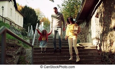 A young family with small daughter walking down the stairs...