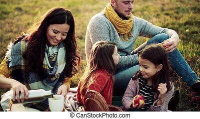 A young family with two small children having picnic in autumn nature.