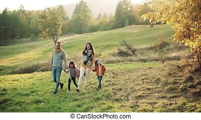 A young family with two small children walking in autumn nature. Slow motion.