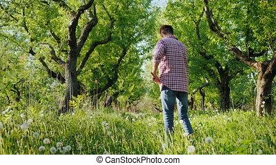 A young farmer mows the grass in an apple garden. Organic ...
