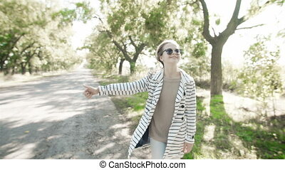 A young fashionable girl on the road is catching a car. A...