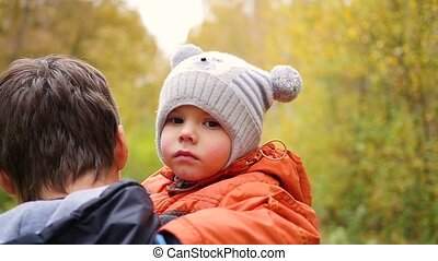 A young father holds his child in his arms. Tenderness and embrace of the beloved father.