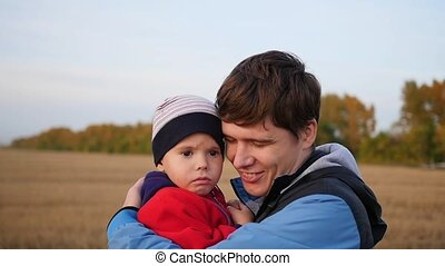 A young father holds his child in his arms. Tenderness and embrace of the beloved father. Outdoor activities