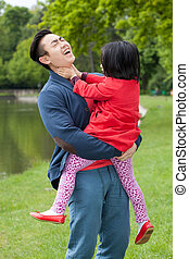 A young father holds on hands of his daughter