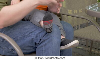 A young father takes off his toddler son's shoes and tickles...