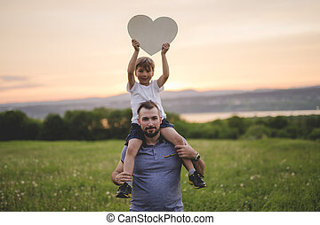 Young father walking with his young son in the meadow at the sunset