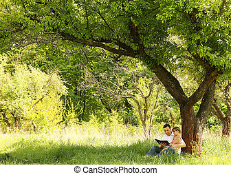 young father with his little daughter reading the Bible - a ...