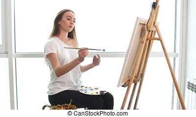 A young female artist painting picture on canvas with blue oil paints in her workshop.